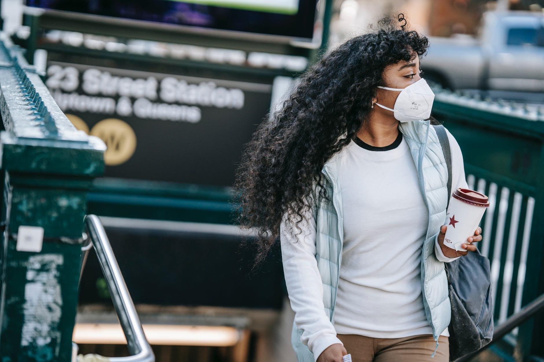 black woman with takeaway coffee leaving metro station